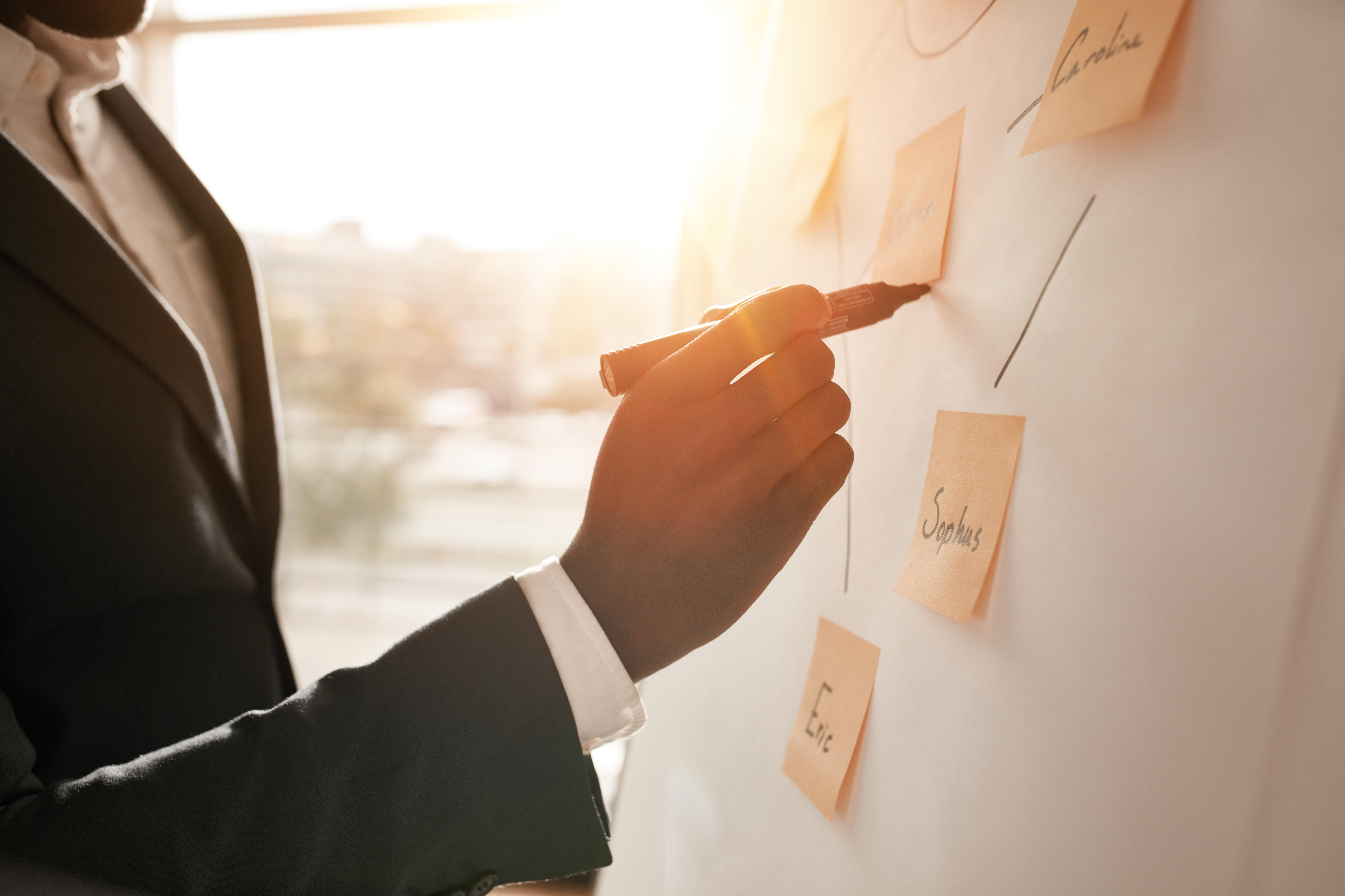 Cropped shot of businessman putting his ideas on white board during a presentation in conference room. Focus in hands with marke